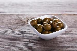 grüne Oliven in der Schüssel auf grauem hölzernem Hintergrund foto