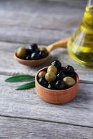 grüne und schwarze Oliven in der Schüssel auf grauem hölzernem Hintergrund foto