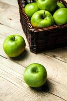 Obst. Äpfel in einem Korb auf Holztisch foto
