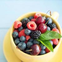 köstliche frische Beeren auf blauem hölzernem Hintergrund foto