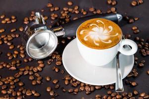 Kaffee spät Tasse und Bohnen auf einem schwarzen Hintergrund.