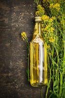 Flasche Rapsöl auf rustikalem hölzernem Hintergrund, Draufsicht foto