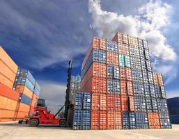 Gabelstapler, der die Containerbox auf der Werft mit blauem Himmel handhabt foto