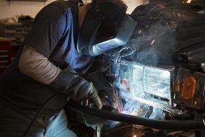 Mann schweißt die Stoßstange eines Fahrzeugs foto