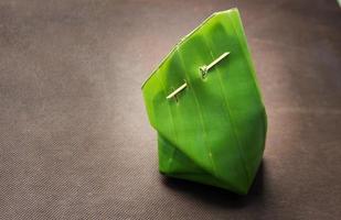 thailändische Dessertverpackung mit Bananenblatt und Holzstab foto