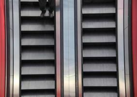 Rolltreppe Zwei-Wege-Nahaufnahme Detail mit Beinen foto