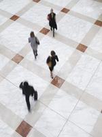 verschwommene Geschäftsleute, die auf Fliesenboden gehen foto
