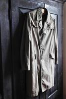 Großvater Vintage Regenmantel auf einem hölzernen Kleiderbügel auf einem schwarzen Kleiderschrank foto