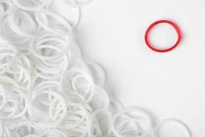 ein roter Gummiring unter einer Vielzahl weißer Ringe