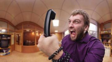 wütender Mann spricht am Telefon foto