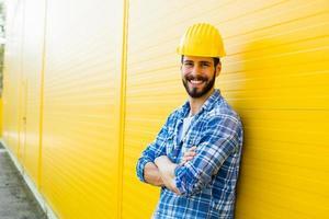 erwachsener Arbeiter mit Helm an gelber Wand foto