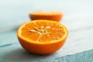 Orangenscheibe auf blauem Holz, Vintage-Ton, Weichzeichner foto