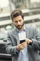 Mann bestellt ein Taxi von seinem Handy foto