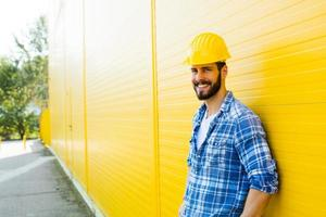 erwachsener Arbeiter mit Helm an gelber Wand