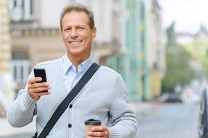 angenehmer Mann, der auf der Straße steht foto