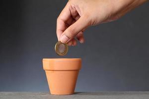 eine Münze in den Boden pflanzen foto