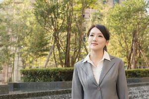 asiatische Geschäftsfrau, die in der Stadt denkt foto