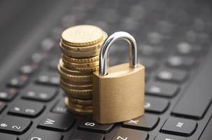 Vorhängeschloss und Münzen auf Laptop-Tastatur foto