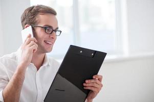 Der hübsche junge Geschäftsmann kommuniziert am Telefon foto