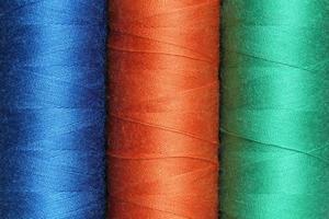 drei Spulen aus farbigen Polyesterfäden