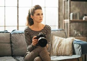 Frau mit DSLR-Fotokamera, die in der Dachbodenwohnung sitzt foto