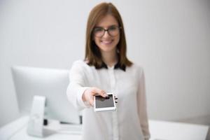 Geschäftsfrau gibt Smartphone vor der Kamera foto