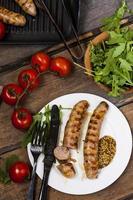 Würstchen auf dem Grill mit Tomaten und Rucola foto