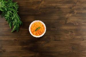 Bund frische Karotten mit grünen Blättern auf Holz