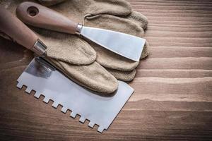 Farbschaber und Spachtel mit Arbeitshandschuh foto