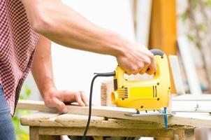 junger Mann Zimmermann, der mit elektrischem Puzzle und Holz arbeitet foto