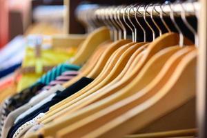 Vielzahl von Kleidungsstücken hängen auf Gestell in Boutique foto