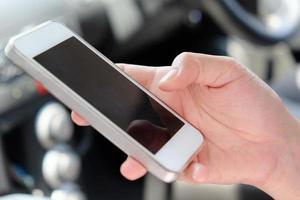 Frauen, die ein Handy im Auto benutzen foto