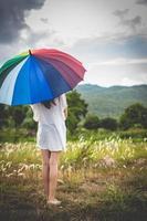 asiatisches Mädchen, das auf jemanden mit Regenbogen wartet