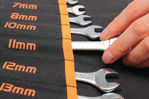 Hand der Frau und Satz Werkzeuge in der schwarzen Abdeckung foto