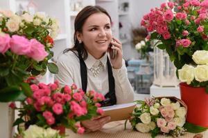 Porträt des lächelnden Floristen, der am Telefon spricht foto