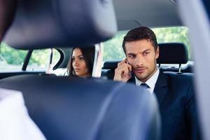 Geschäftsmann, der im Auto am Telefon spricht foto