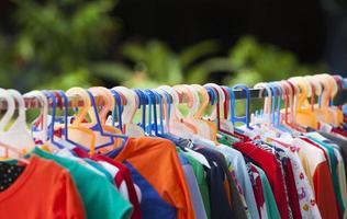 Kleidung hängt in einem Regal foto