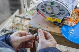 Glasfasertechniker, der Fasern zum Spleißen vorbereitet 2 foto
