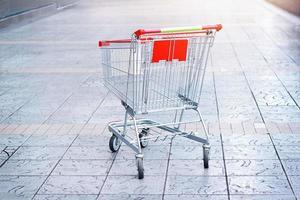 leerer Einkaufswagen auf dem Bodenhintergrund