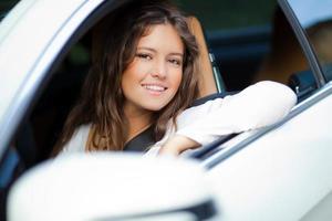schöne junge Frau, die ihr Auto fährt foto