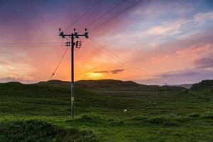 Telefon- oder Stromleitung auf den Feldern bei Sonnenuntergang foto
