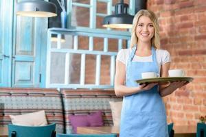 angenehme Kellnerin hält Tablett foto