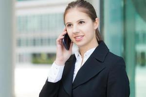 schöne junge Frau, die am Telefon spricht foto
