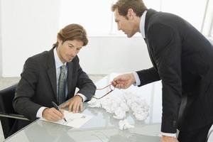 wütender Geschäftsmann mit männlichem Kollegen, der auf Papier schreibt