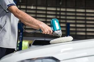 Autopolierserie: Arbeiter wächst weißes Auto foto