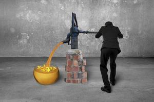 Mann, der goldene Sandwährungssymbole Retro Pump Beton Roo zeichnet foto