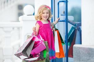 kleines Mädchen mit Einkaufstüten geht in den Laden foto