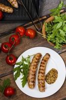 Würstchen auf dem Grill mit Tomaten und Rucola