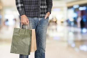 aufregender junger Einkaufsmann halten Taschen, Nahaufnahmeporträt mit Copyspace. foto