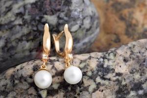 goldene Ohrringe mit Diamanten und Perlen auf den Natursteinen foto